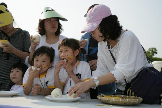 성주참외페스티벌에 참가한 엄마와 아이들이 성주참외를 먹고 있다. 성주참외에는 엽산이 풍부해 산모와 태아 건강에 도움을 준다. 성주군 제공