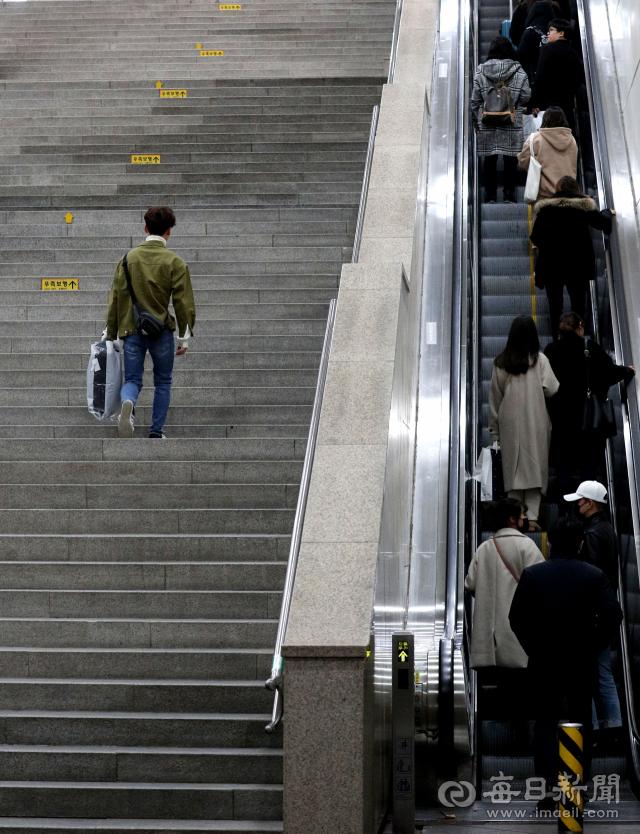 계단을 오르는 한 사람과 에스컬레이터에 탄 많은 사람들의 모습이 눈길을 끈다. 전문가들은