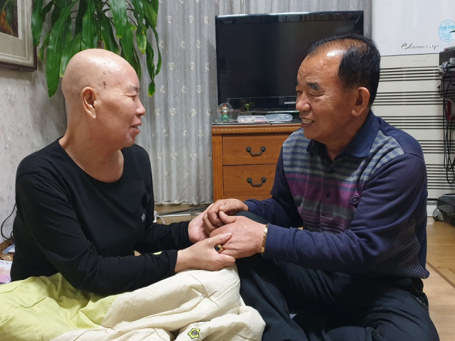 혈액암에 걸려 머리카락이 다 빠진 손연희(63·가명) 씨가 남편 전필만(66· 가명) 씨 손을 붙잡고 있다. 이들은 장애인이 된 아들, 손자 손녀 까지 책임져야할 상황이지만 당장 치료비도 없는 생활고를 겪고 있다. 이주형 기자