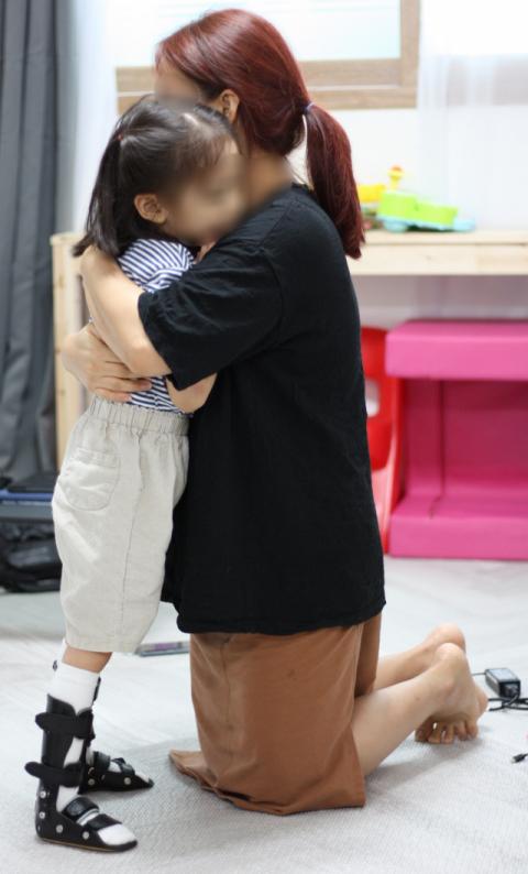 이채진(39·가명) 씨가 예슬이(5·가명)와 걷기연습을 하다 말고 딸을 꼭 안아주고 있다. 모녀는 전문적인 치료 대신 집에서 틈틈이 다리운동을 하지만 예슬이는 두 다리로 10초도 서 있지 못한다. 이주형 기자.