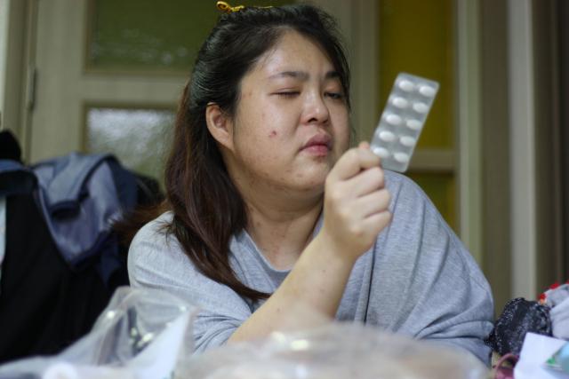 황상희(28) 씨가 약을 보고 있다. 중증근무력증 합병증으로 시력이 급격히 나빠진 그는 가까운 물체도 뿌옇게 보인다. 이주형 기자.