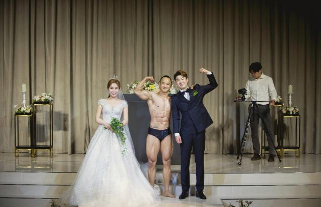 한 체육인이 결혼식장에서 육체미 공연을 펼친 뒤 신랑신부와 포즈를 취하고 있다. 고구마웨딩 제공