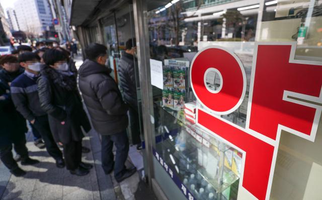 지난 11일 서울 시내의 한 약국에서 시민들이 공적 마스크를 구매하기 위해 기다리고 있다. 연합뉴스
