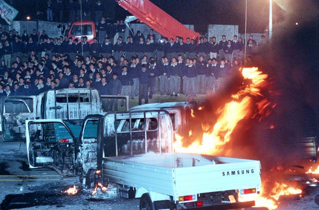 삼성상용차 퇴출 발표 직후 분노한 직원들이 생산된 트럭을 불태우며 시위를 벌이고 있는 모습. 매일신문DB