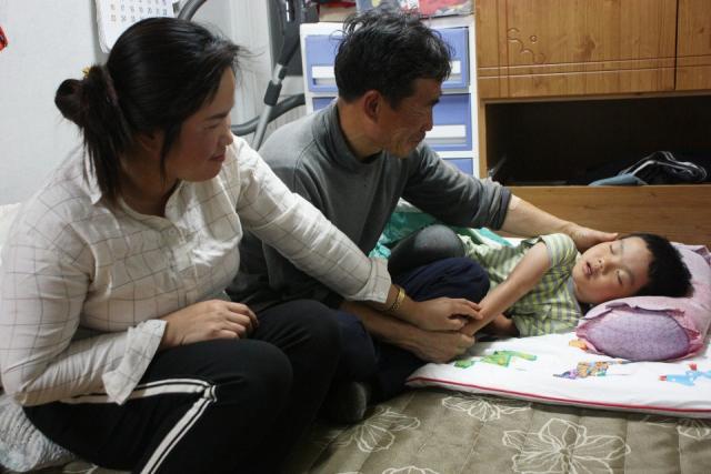 장진철(가명·54) 씨 부부가 잠에 빠진 막내아들(5)을 지켜보고 있다. 이주형 기자