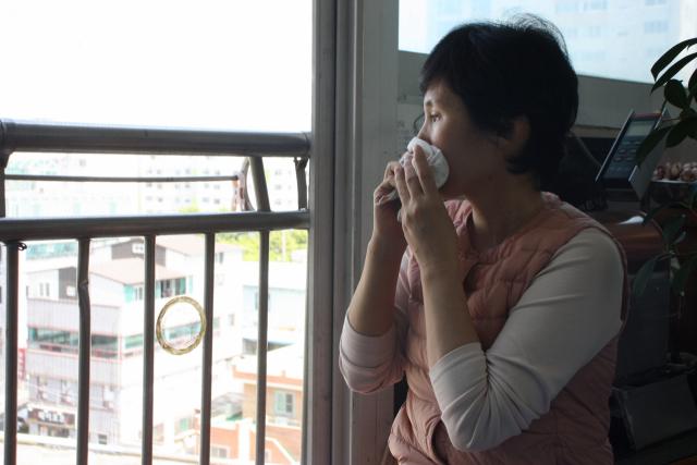 이민영(가명·50) 씨가 기침을 하면서 창밖을 바라보고 있다. 이주형 기자