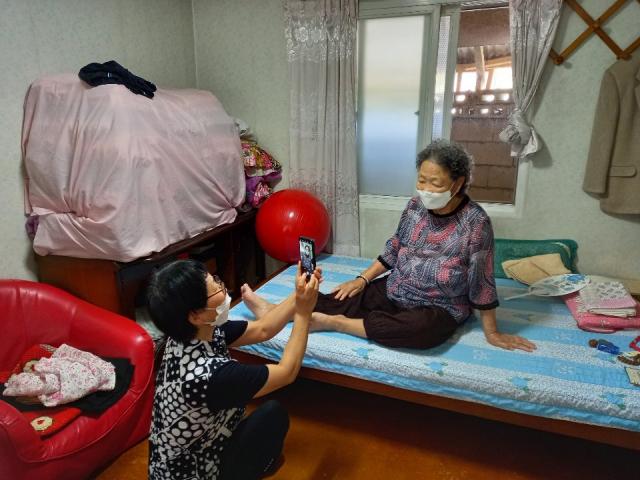 경북 의성군의 생활지원사가 홀몸노인의 집을 방문해 영상을 촬영하고 있다. 이 영상은 추석에 고향을 오지 못하는 객지의 자녀들에게 배달된다. 의성군 제공