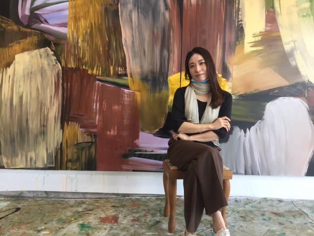 박경아 추상표현주의 화가가 자신의 화실에 걸린 대형작품 앞에서 포즈를 취하고 있다.