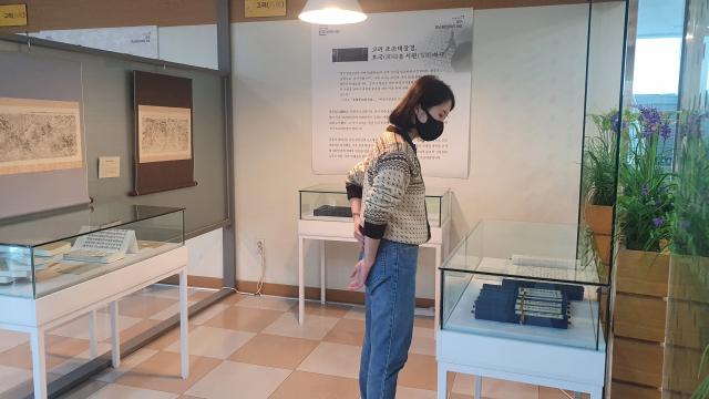 한 관람자가 용학도서관 특별전시실에 전시된 복원된 초조대장경을 살펴보고 있다. 용학도서관 제공
