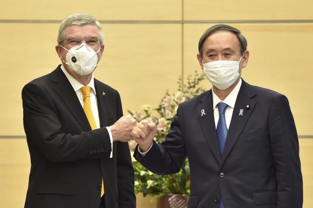 스가 요시히데(오른쪽) 일본 총리가 지난 16일 도쿄 총리관저에서 자국을 방문한 토마스 바흐(왼쪽) 국제올림픽위원회(IOC) 위원장을 영접하면서 '주먹 인사'를 나누고 있다. 스가 총리와 바흐 위원장은 이날 회담에서 신종 코로나바이러스 감염증(코로나19) 탓에 연기된 도쿄올림픽과 패럴림픽의 내년 7월 개최를 재확인했다. 연합뉴스