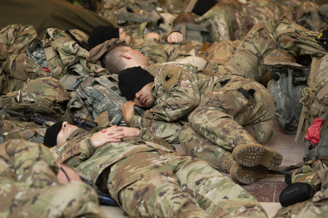 미국 워싱턴DC의 연방의회의 의사당을 경비하는 주방위군 병사들이 13일(현지시간) 방문객 센터에서 포개져 휴식을 취하고 있다. 연합뉴스