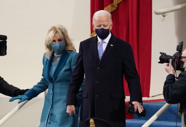 조 바이든 제 46대 미국 대통령이 20일(현지시간) 워싱턴DC 미 의회의사당에 마련된 취임식장에 부인 질 바이든 여사와 함께 입장하고 있다. 로이터