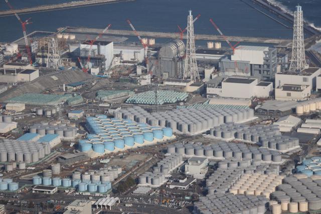 일본 정부는 13일 동일본 대지진 때 원전 사고를 일으킨 후쿠시마 제1 원전의 탱크에 보관 중인 오염수를 해양에 방출하기로 각료회의를 통해 결정했다고 현지 언론이 보도했다. 방류 예정인 오염수는 125만t이 넘는다. 사진은 지난 2월 14일 촬영한 도쿄전력의 후쿠시마 제1 원전(위)과 오염수 탱크(아래)의 모습. [지지통신 제공] 연합뉴스