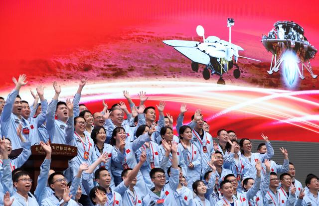 중국 수도 베이징의 항공관제센터에서 15일 오전 자국의 첫 화성 무인 탐사선 '톈원(天問) 1호'가 화성 유토피아 평원에 성공적으로 착륙했다는 소식에 기술진이 손을 흔들며 환호하고 있다. 중국국가항천국(CNSA)은 약 7개월간의 비행 끝에 지난 2월 화성 궤도에 진입한 톈원 1호가 이날 화성 표면에 안착했다고 확인했다. 연합뉴스