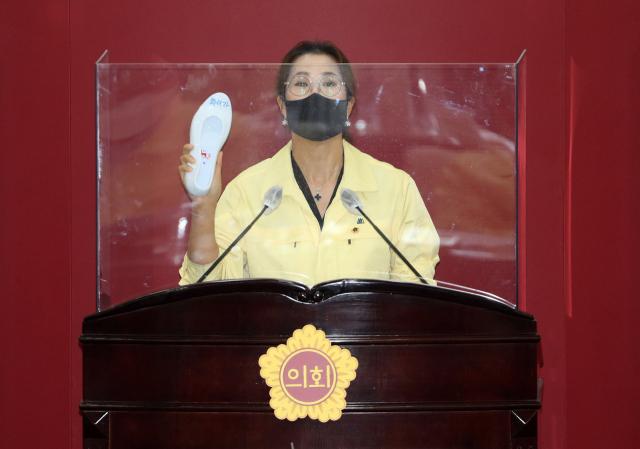 이진련 시의원이 16일 대구시의회에서 열린 283회 정례회 본회의에서 화이자 백신 도입 관련 시정질문을 하며 화이자라고 적힌 백신(흰 고무신)을 들어 보이고 있다. 연합뉴스