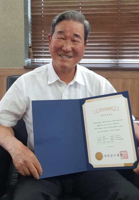 김영만 우성철강㈜ 회장이 대한골프협회 공인 '에이지 슈트' 증서를 들어 보이며 웃고 있다. 최두성 기자