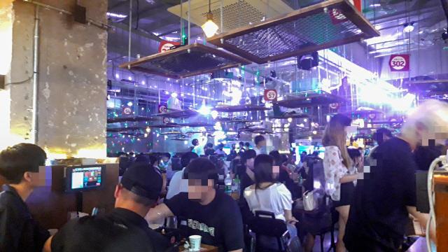 지난 7월 10일 대구 동성로 한 주점에서 젊은이들이 다닥다닥 붙어 앉아 마스크 없이 술을 마시고 있다. 윤정훈 기자