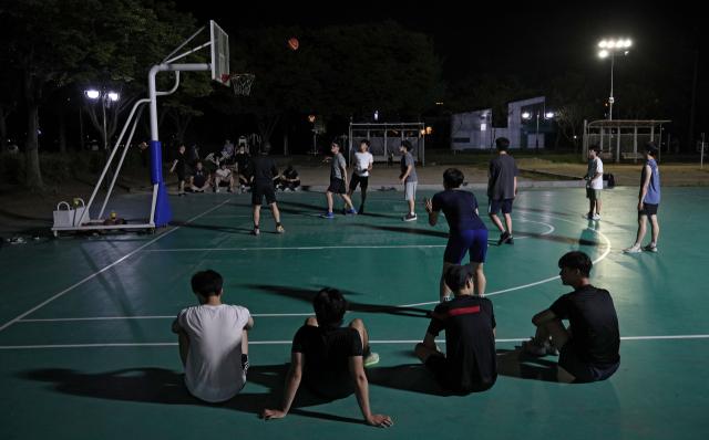 한낮의 뜨거운 열기가 밤까지 이어진 열대야 현상이 나타난 지난 13일 밤 대구 수성못을 찾은 시민들이 농구를 하며 더위를 이겨내고 있다. 김영진 기자 kyjmaeil@imaeil.com