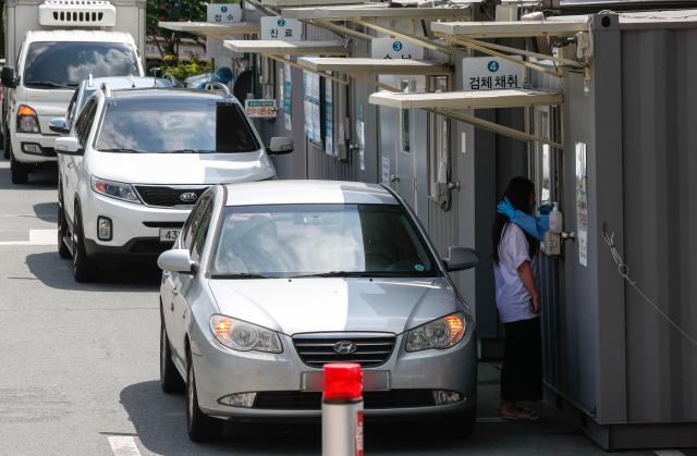 14일 오전 대구의료원 승차형 선별검사소에서 진단검사를 받으려는 시민들이 차량 안에서 차례를 기다리고 있다. 이날 0시 기준 대구에서는 52명의 신규 확진자가 발생했다. 우태욱 기자 woo@imaeil.com
