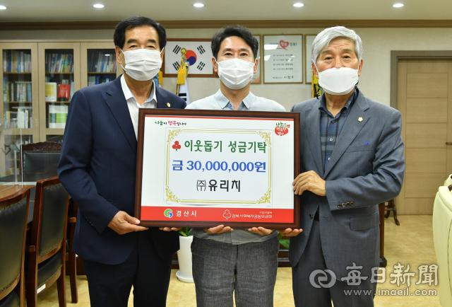 ㈜유리치 김재식 대표이사(가운데)가 19일 경산시청을 방문해 이웃돕기 성금 3천만원을 기탁했다.