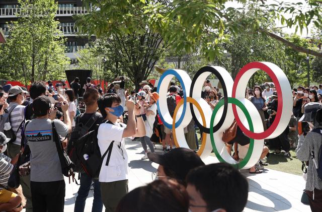 도쿄올림픽 개막일인 23일 일본 도쿄 신주쿠(新宿) 국립경기장에서 앞 광장에서 일본 시민들이 오륜기 조형물을 배경으로 사진 찍고 있다. 이번 개막식은 신종 코로나바이러스 감염증(코로나19) 확산에 따라 무관중으로 진행된다. 연합뉴스