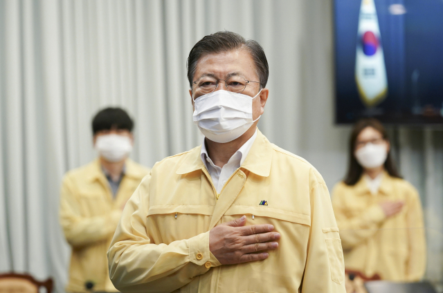 문재인 대통령이 20일 오전 청와대에서 열린 영상 국무회의에서 국기에 경례하고 있다. 연합뉴스