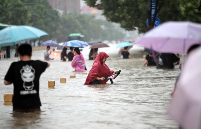 20일 중국 중부 허난성 성도인 정저우에 폭우가 쏟아지는 가운데 시민들이 물에 잠긴 거리를 걷고 있다. 이날 정저우에서는 기록적인 폭우로 지하철에 갇힌 승객 12명이 숨졌으며, 주민 10만 명이 긴급 대피했다. 연합뉴스
