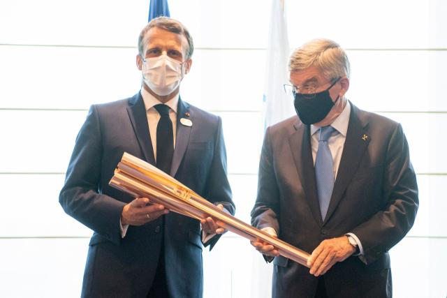 23일 도쿄올림픽 개회식에 앞서 일본 도쿄에서 에마뉘엘 마크롱(왼쪽) 프랑스 대통령이 토마스 바흐 국제올림픽위원회(IOC) 위원장으로부터 성화봉을 건네받고 있다. 오는 2024년 하계올림픽은 프랑스 파리에서 개최된다. 연합뉴스