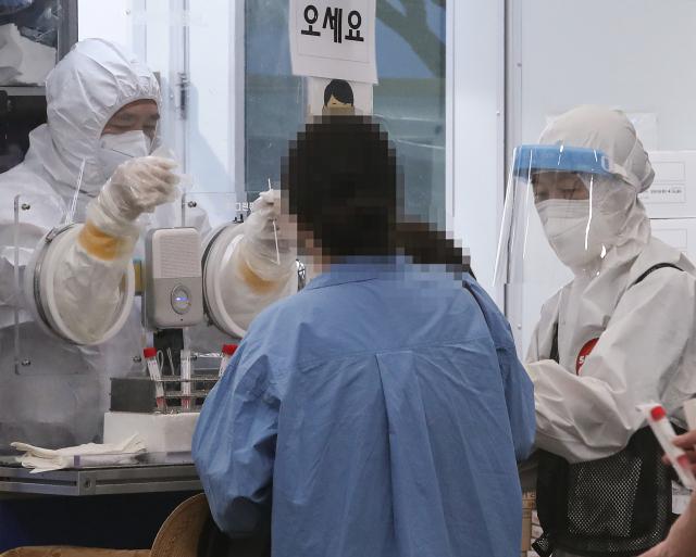 24일 오전 서울 송파구 송파구보건소에 마련된 신종 코로나바이러스 감염증(코로나19) 선별진료소에서 의료진이 검사를 진행하고 있다. 중앙방역대책본부는 이날 0시 기준으로 신규 확진자가 1천629명 늘어 누적 18만7천362명이라고 밝혔다. 특히 수도권의 확산세가 지속 중인 상황에서 최근 들어 비수도권의 환자 발생도 눈에 띄게 증가하면서 전국적 대유행 가능성이 점점 커지고 있다. 연합뉴스