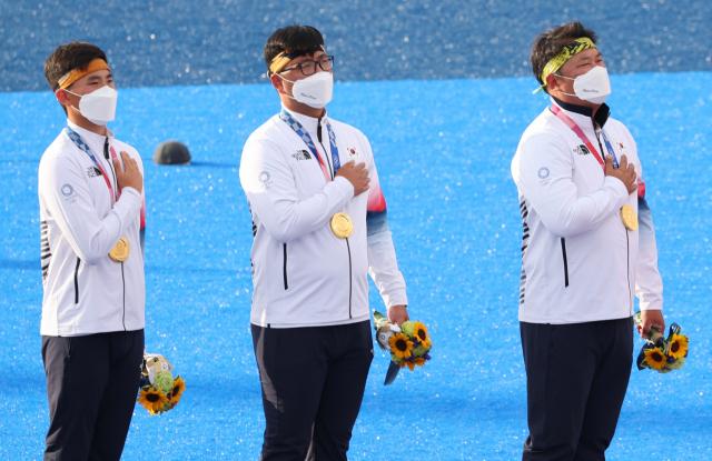 26일 도쿄올림픽 남자 양궁 단체전에서 우승한 한국 선수들이 일본 유메노시마 공원 양궁장 시상대에서 국기에 경례를 하고 있다. 연합뉴스