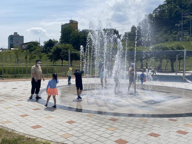 지난 23일 개장한 안동 강변시민공원 어린이물놀이장 내 설치된 바닥분수에서 아이들과 보호자가 물놀이를 즐기고 있다. 안동시 제공