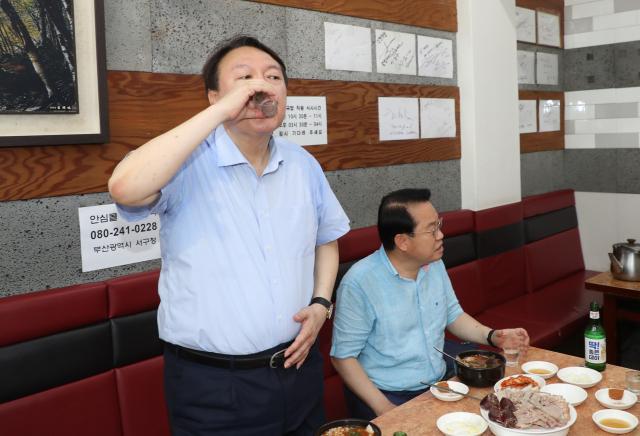 윤석열 전 검찰총장이 27일 낮 부산 서구에 있는 한 국밥집에서 국민의힘 부산 국회의원들과 식사하면서 소주를 마시고 있다. 연합뉴스
