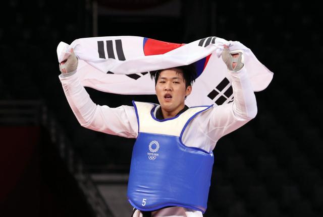 27일 일본 마쿠하리 메세홀에서 열린 도쿄올림픽 남자 태권도 80㎏ 초과급 동메달 결정전 한국 인교돈-슬로베니아 트라이코비치. 인교돈이 승리 후 태극기를 흔들고 있다. 연합뉴스