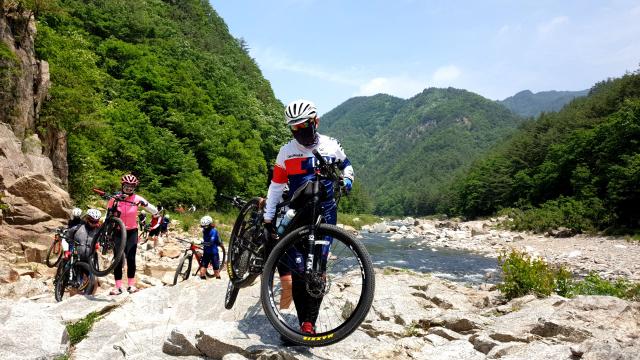 세평하늘길에서 길이 끊어지자 자전거 탐사팀원들이 자전거를 끌고 계곡을 건너고 있다.