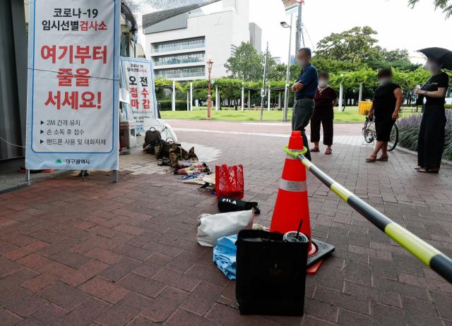 28일 대구국채보상운동기념공원 코로나19 임시선별검사소에서 오후 검사소 운영 시작에 앞서 대기 순서를 표시하기 위한 시민들의 소지품들이 바닥에 놓여져 있다. 우태욱 기자 woo@imaeil.com