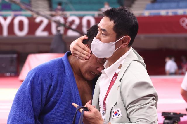 29일 일본 도쿄 무도관에서 열린 도쿄올림픽 유도 남자 -100 kg급 결승 경기에서 한국 조구함이 일본 에런 울프에게 패한 뒤 눈물을 흘리자 송대남 코치가 위로하고 있다. 연합뉴스