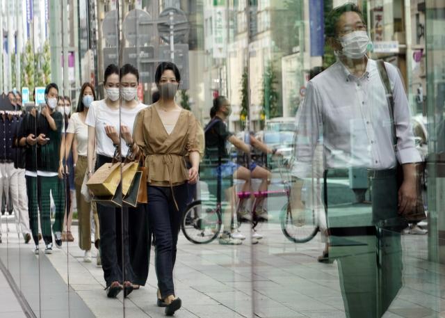 일본 도코의 긴자 거리에서 29일 마스크를 쓴 행인들의 모습이 쇼윈도우에 투영되고 있다. 이날 일본의 신종코로나바이러스감염증(코로나19) 신규 확진자는 처음으로 1만명 선을 돌파했다. 연합뉴스