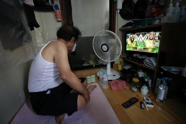 지난 25일 서울시 중림동 한 쪽방촌에서 거주자가 선풍기를 켜고 TV를 보고 있다. 연합뉴스