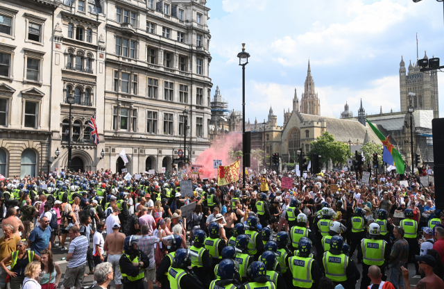19일(현지시간) 영국 런던의 의회광장에서 경찰이 신종 코로나바이러스 감염증(코로나19) 관련 봉쇄에 반대하는 시위대를 막아서고 있다. 영국은 델타 변이 확산으로 하루 신규 확진자가 5만 명을 넘어선 가운데 이날 방역 규제를 대거 해제했다. 자가격리 중인 보리스 존슨 총리는 오는 9월 말부터 나이트클럽 등 사람이 붐비는 장소에 가려면 백신접종을 완료했다는 사실을 증빙하도록 하는 방안을 도입하겠다고 밝혔다. 연합뉴스