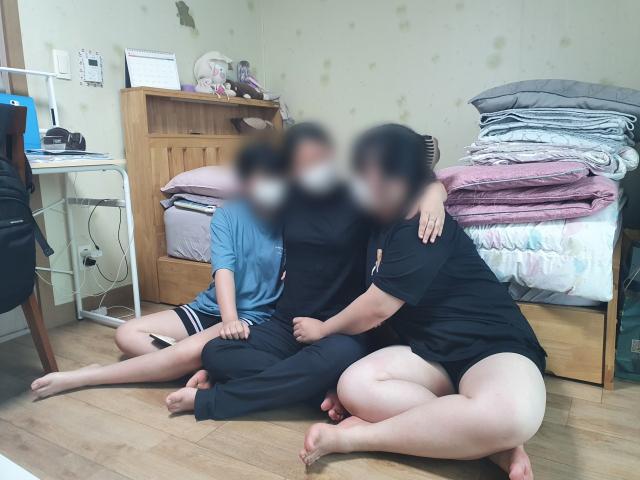 큰 언니 곽민정(가명·21·가운데) 씨에게 둘째 여동생 민주(가명·19) 양과 셋째 여동생 민희(가명·13) 양이 안겨있다. 배주현 기자