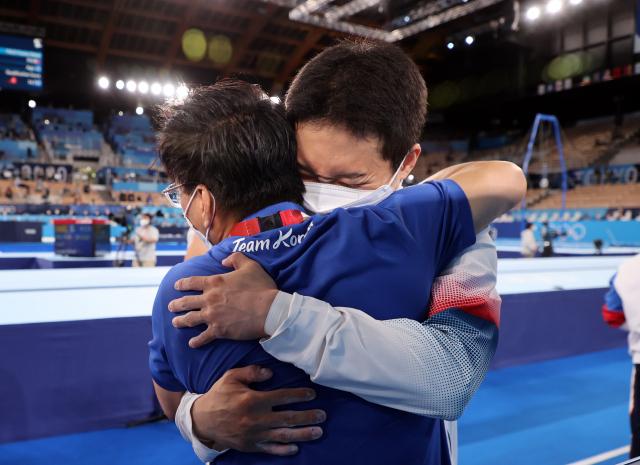 2일 일본 아리아케 체조경기장에서 열린 도쿄올림픽 남자 기계체조 도마 결선에서 신재환이 다른 선수들의 경기 결과를 확인한 뒤 코치와 기뻐하고 있다. 연합뉴스