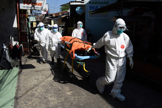 인도네시아의 지방도시 반둥에서 지난달 18일 보건 요원들이 자택에 격리됐다가 숨진 신종코로나바이러스감염증(코로나19) 사망자의 시신을 옮기고 있다. 연합뉴스