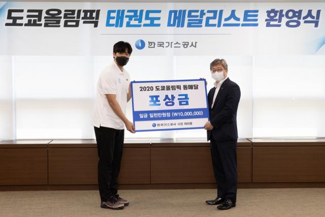 채희봉(오른쪽) 가스공사 사장이 인교돈 선수에게 포상금을 지급하고 있다. 가스공사 제공