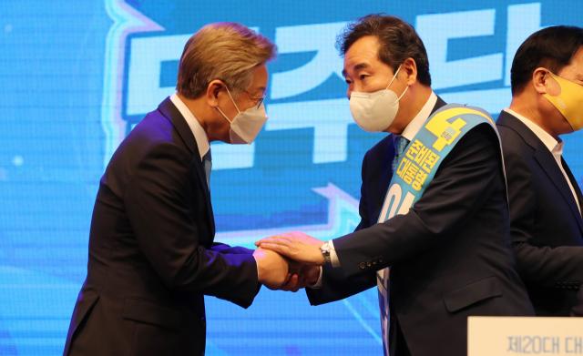이재명 경기지사(왼쪽)가 충북 청주시 서원구 CJB컨벤션센터에서 이낙연 후보자와 인사하고 있다. 연합뉴스