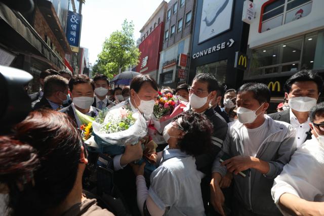 국민의힘 대권주자인 윤석열 전 검찰총장이 11일 오후 대구 중구 동성로를 찾아 지지자로부터 꽃을 받고 있다. 안성완 기자 asw0727@imaeil.com