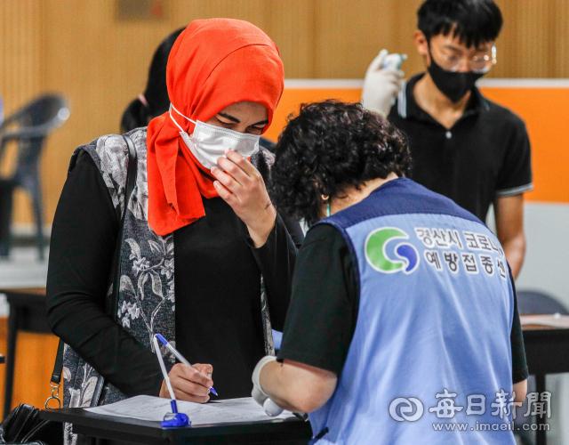 추석 연휴를 하루 앞둔 17일 오후 경산시 예방접종센터에서 한국어가 서툰 한 외국인이 접종센터 관계자의 도움을 받아 예진표를 작성하고 있다. 이날 0시 기준 경북 지역 코로나19 백신 1차 접종률은 인구대비 70.5%로, 도민 262만3천 여 명 가운데 183만 여 명이 1차 접종을 완료했다. 우태욱 기자 woo@imaeil.com