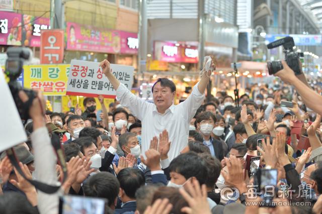 9월 17일 윤석열 국민의힘 대선 예비후보가 포항 죽도시장에서 빼곡히 몰려든 지지자들에게 둘러 쌓인 채 화답의 손을 흔들고 있다. 신동우 기자