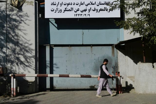 아프가니스탄 수도 카불에서 17일(현지시간) 한 남성이 탈레반에 의해 폐쇄된 전 정부의 여성부 건물 입구를 지나고 있다. 여성부 건물 현판 자리에는 '기도·훈도 및 권선징악부' 간판이 걸려 있다. 권선징악부는 탈레반의 과거 통치기(1996∼2001년)에 '도덕 경찰'로 활동하며 샤리아(이슬람 율법)로 엄격하게 사회를 통제했던 부서다. 연합뉴스