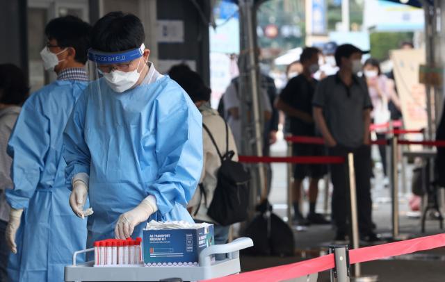 신종 코로나바이러스 감염증(코로나19) 신규 확진자 수가 1천605명을 기록한 20일 오전 서울역 코로나19 선별진료소에서 의료진이 검사를 준비하고 있다. 연합뉴스