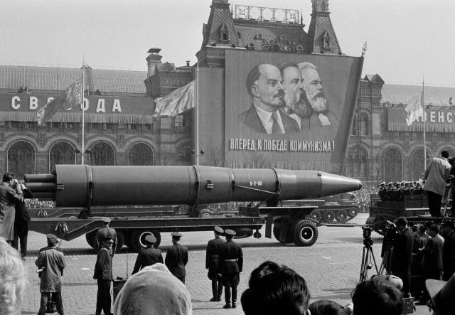 1963년 소비에트군의 로켓이 노동절 퍼레이드에서 레닌, 엥겔스, 마르크스의 얼굴이 그려진 휘장 앞을 지나가고 있다.